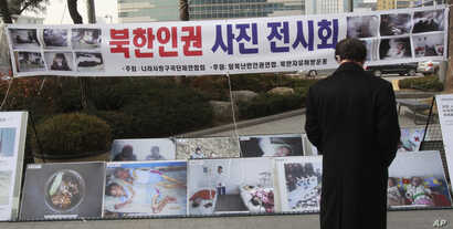 FILE - A man watches photos showing North Korean children suffering from famine at a photo exhibition in Seoul, South Korea, Feb. 27, 2014.