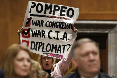 Retired U.S. Army Col. Ann Wright, center, protests the nomination of CIA Director Mike Pompeo, front right, for secretary of state, as he waits to testify before the Senate Foreign Relations Committee during a confirmation hearing on his nomination ...