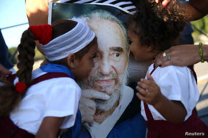 Marian Martin (L) and her sister Chanel (R) kiss a portrait of Cuba's late President Fidel Castro after paying tribute to Castro along with their mother at the Jose Marti Memorial in Revolution Square in Havana, Nov. 29, 2016.