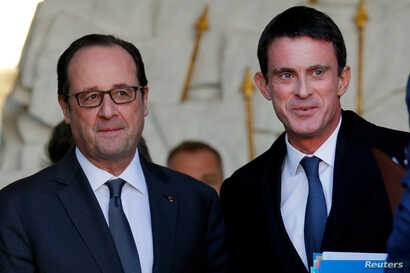 French President Francois Hollande (left) speaks with Prime Minister Manuel Valls as he leaves a weekly cabinet meeting. Valls is widely expected to announce a run in the coming days.