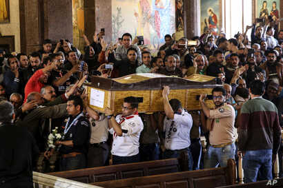 Men carry the coffin of a victim during the funeral for those killed in a Palm Sunday church attack in Alexandria Egypt, at the Mar Amina church, April 10, 2017.