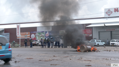 Zimbabwe's police watch tires burning as protesters try to block a road in Harare during (January 2019)  protests over a 150 percent fuel increase.