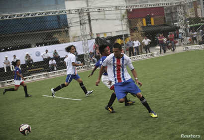 """Players from Costa Rica and the Philippines (in blue shirts) compete in a soccer match during the """"Street Soccer World Cup"""" in Sao Paulo, Brazil, July 7, 2014."""