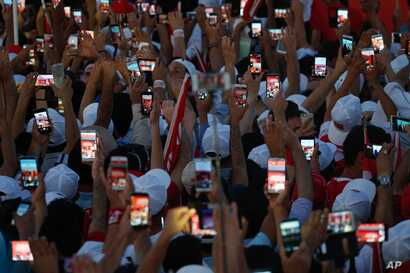 Turkish people use their cell phones to take images before the speech of President Recep Tayyip Erdogan at the Democracy and Martyrs' Rally in Istanbul, Aug. 7, 2016.