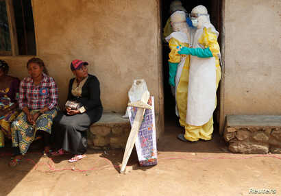 Healthcare workers enter a house where a baby suspected of dying of Ebola is, during the funeral in Beni, North Kivu Province of Democratic Republic of Congo, Dec. 18, 2018.