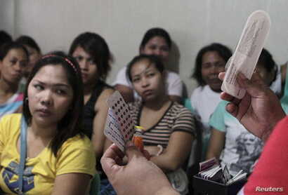FILE - A community health worker holds up contraceptives during a lecture on family planning at a reproductive health clinic run by an NGO in Tondo city, metro Manila, January 12, 2016.