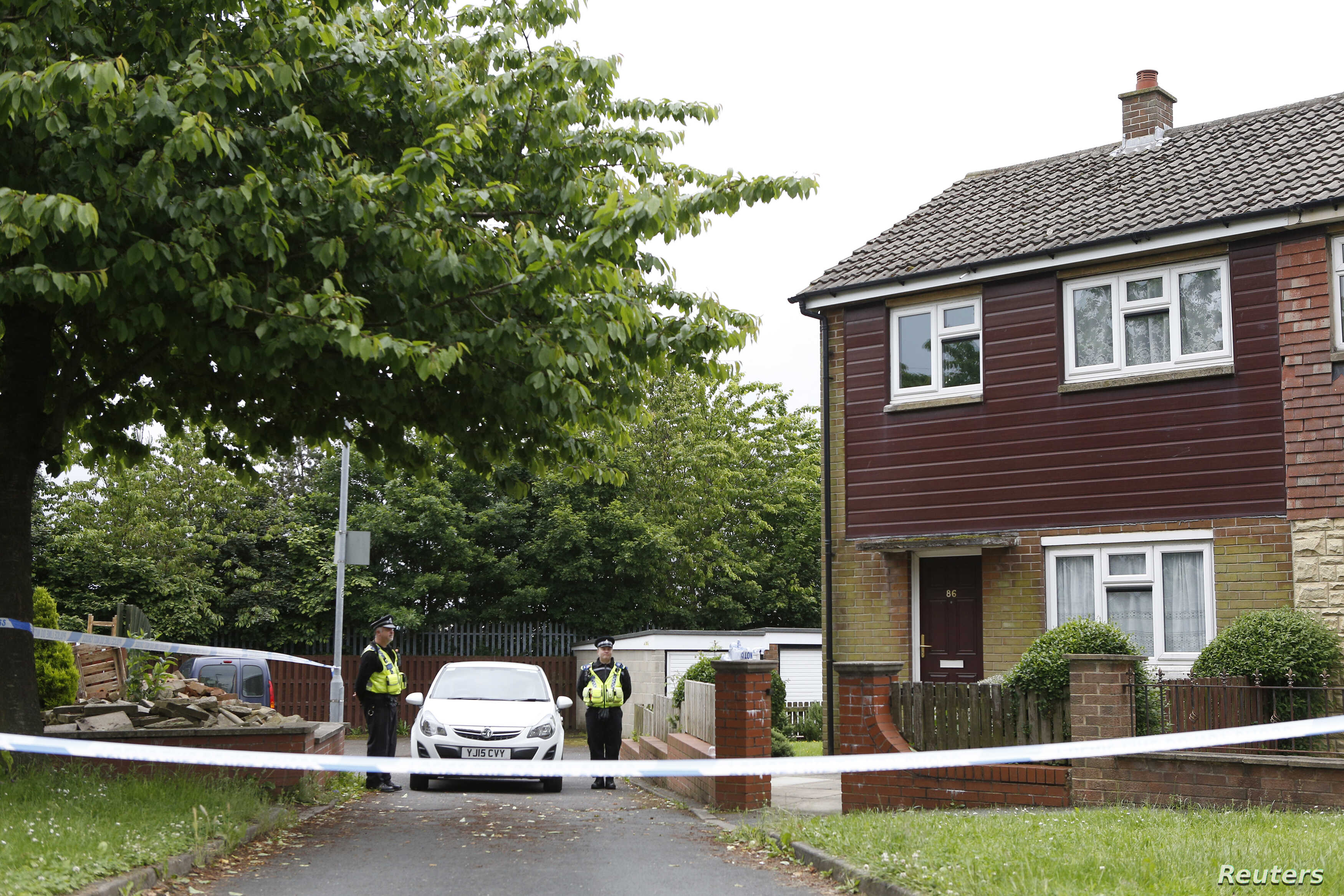 Police officers stand outside the home of Thomas Mair, named by local media as the man who was arrested after Labour MP Jo Cox was murdered in her constituency near Leeds, Britain, June 17, 2016.