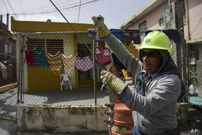 FILE -  Ezequiel Rivera works with the Puerto Rico Electric Power Authority to restore distribution lines damaged by Hurricane Maria in the Cantera community of San Juan, Puerto Rico, Oct. 19, 2017.
