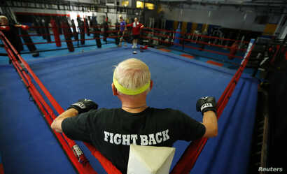 Parkinson's patient Ron Addison waits for his training session in the ring during his Rock Steady Boxing session in Costa Mesa, California September 16, 2013. According to the Parkinson's Disease Foundation, research has shown that exercise can trans...