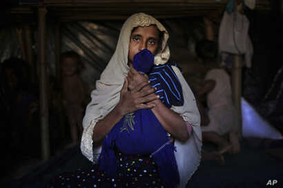 In this Nov. 26, 2017, photo, Jamila Begum, 35, caresses a favorite shirt and school bag of her late son who was killed by members of Myanmar's armed forces accused of massacring civilians in in Myanmar's Rakhine State.