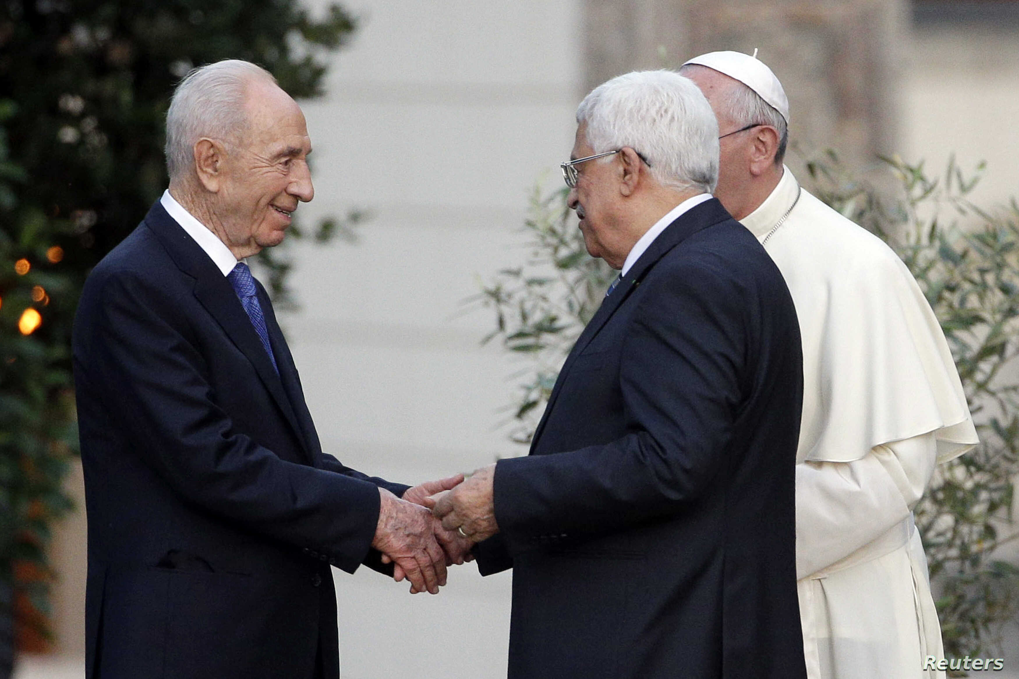 Israeli President Shimon Peres shakes hands with Palestinian President Mahmoud Abbas as Pope Francis watches after a prayer meeting at the Vatican, June 8, 2014.