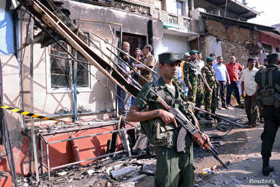 Sri Lanka's army soldiers stand guard near a burned house after a clash between two communities in Digana, central district of Kandy, Sri Lanka, March 6, 2018.