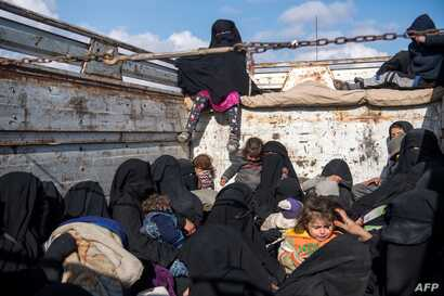 Women and children fleeing from the last Islamic State group's tiny pocket in Syria sit in the back of a truck near Baghuz, eastern Syria, Feb. 11, 2019.
