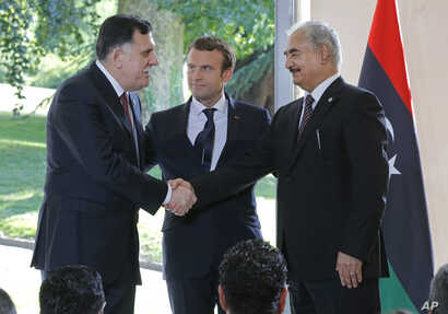 Libya's Prime Minister Fayez al-Sarraj of the U.N.-backed government (L), and General Khalifa Hifter of the Egyptian-backed commander of Libya's self-styled national army shake hands as France's President Emmanuel Macron stands between after a declar...