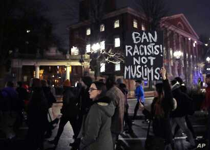 Several hundred people march past the gates of Harvard Yard at Harvard University while protesting the travel ban in Cambridge, Mass., March 7, 2017.