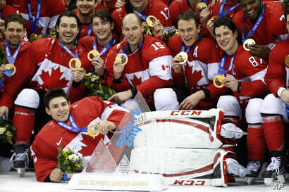 Canada players pose for pictures after they beat Sweden 3-0 in the men's ice hockey gold medal game at the 2014 Winter Olympics, Feb. 23, 2014, in Sochi, Russia.