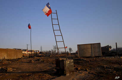 National flags fly over the scorched landscape of Chile's Santa Olga community, Jan. 31, 2017.