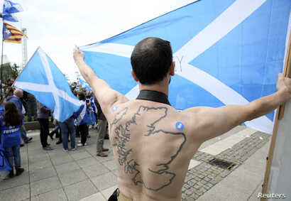 """A """"Yes"""" supporter with a tattoo of Scotland on his back holds a Saltire flag at a rally outside the BBC in Glasgow, Scotland, Sept. 14, 2014."""