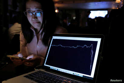 A woman watching the Brexit vote in The Churchill Tavern, a British themed pub, reacts as a graph shows the British Pound falling in value following the announcement that Britain would leave the European Union, in the Manhattan borough of New York, U...