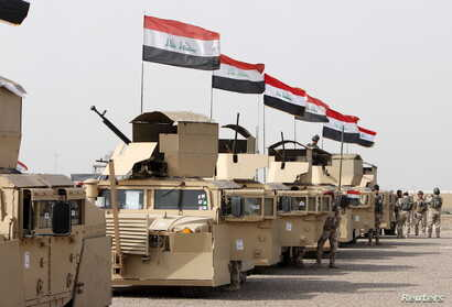 Iraqi security forces ride in vehicles travelling to Mosul to eject Islamic State militants on Feb. 21, 201.6