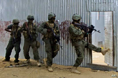 FILE - Somali soldiers search through homes for al-Shabaab fighters, during an operation in Ealsha Biyaha, Somalia, June, 2, 2012. On Tuesday, Somali forces attacked a base of the militant group north of Kismayo.