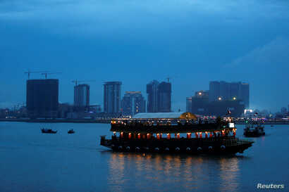 """FILE - A boat passes buildings under construction on Diamond Island also known as """"Koh Pich,"""" as seen from Tonle Chaktomuk River in Phnom Penh, Cambodia, May 22, 2018."""