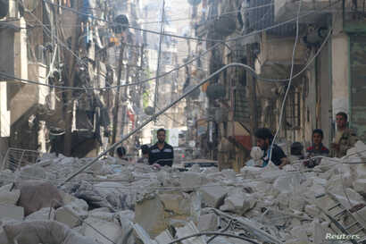 People inspect a site hit by an airstrike in the rebel held area of Aleppo's al-Sukari district, Syria, May 30, 2016.