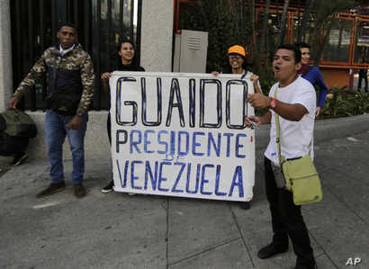 "Anti-government protesters show a sign reading in Spanish ""Guaido President of Venezuela"" after a rally demanding the resignation of President Nicolas Maduro in Caracas, Venezuela, Jan. 23, 2019."