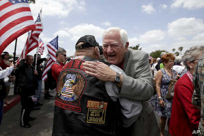 FILE - Former Vietnam POW Orson Swindle, right, gets a hug from Jim Janeway as he arrives to celebrate the 40th reunion for Vietnam POWs at the Richard Nixon Presidential Library & Museum in Yorba Linda, Calif., May 23, 2013.