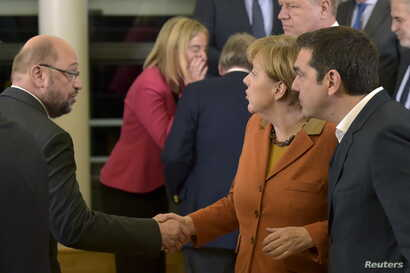 European Parliament President Martin Schulz (L) and Germany's Chancellor Angela Merkel and Greece's Prime Minister Alexis Tsipras (R) chat after a family photo at a meeting over the Balkan refugee crisis with leaders from central and eastern Europe a...