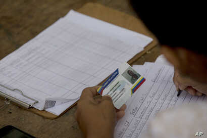 """FILE - A member of the ruling United Socialist Party writes takes note of the """"fatherland card"""" of a voter outside a voting center in Valencia, Venezuela, May 20, 2018. Checkpoints known as """"red points' are set up outside polling centers to confirm p..."""