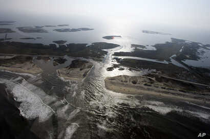 FILE - A flooded road on Hatteras Island, N.C., is shown after Hurricane Irene swept through the area, cutting the roadway in five locations, Aug. 28, 2011. Flooding caused by rising sea levels may end up costing U.S. coastal communities as much mone...