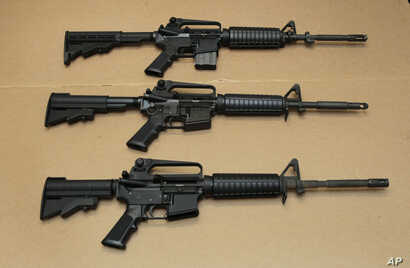 FILE -- Three variations of the AR-15 assault rifle are displayed in Sacramento, Calif. While the guns look similar, the bottom version is illegal in California because of its quick reload capabilities. Omar Mateen used an AR-15 that he purchased leg