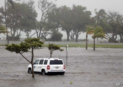 A park officer's vehicle sits in a flooded parking lot at Haulover Park as Hurricane Irma passes through the area, in North Miami Beach, Florida, Sept. 10, 2017.