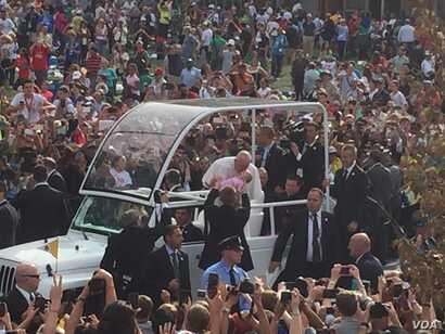 Pope Francis kisses a baby from his popemobile near Independence Hall, Philadelphia, Sept. 26, 2015. (J. Socolovsky/VOA)