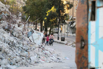 Children are seen playing near the rubble of damaged buildings in the rebel-held Bab al-Hadid neighborhood of Aleppo, Syria, Sept. 14, 2016.