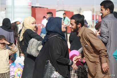 Some families are reunited when they arrive in refugee camps less than a day after running for their lives from IS militants, in Hammem Aleel, Iraq, Feb. 28, 2017. (H. Murdock/VOA)