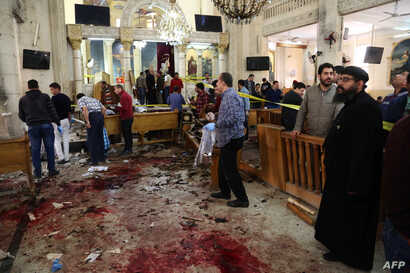 A general view shows people looking at the aftermath following a bomb blast which struck worshippers gathering to celebrate Palm Sunday at the Mar Girgis Coptic Church in the Nile Delta City of Tanta, 120 kilometres (75 miles) north of Cairo, on Apri...