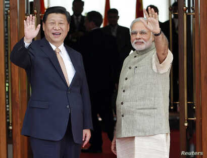 India's Prime Minister Narendra Modi (R) and China's President Xi Jinping wave before their meeting in the western Indian city of Ahmedabad September 17, 2014. Xi arrived in India as the two Asian giants take steps to boost commercial ties. China has