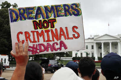 FILE - A woman holds up a signs in support of Deferred Action for Childhood Arrivals, or DACA, during an immigration reform rally at the White House in Washington, Aug. 15, 2017.