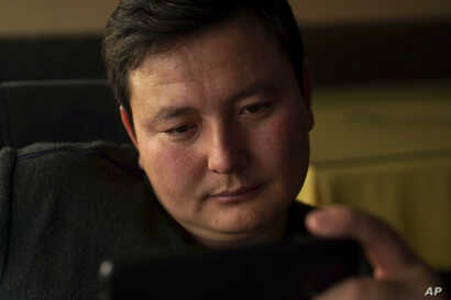 """In this Dec. 9, 2018 photo, Kairat Samarkan, a former detainee in a Chinese internment camp, watches a state television report about what Beijing calls """"vocational training centers"""" in a restaurant in Almaty in Kazakhstan."""