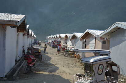 """Bunkhouses"" or temporary housing for people who had been living in evacuation sites since the storm.  Each structure can house up to 24 families of five, Philippines. (Simone Orendain/VOA)"