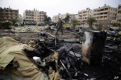 A Russian soldier checks a burned medical tent after rebels launched a mortar shell at a field hospital in west Aleppo, Syria, Dec. 5, 2016. Rebel shelling of the government-held part of Syria's Aleppo city Monday killed a Russian female nurse in a m...