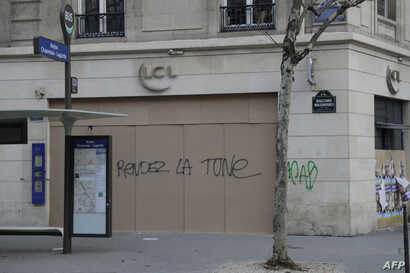"""The words """"Give back the money"""" are written on the facade of a bank in Paris, Dec. 15, 2018, as protesters wearing yellow vests arrive to demonstrate against rising costs of living they blame on high taxes."""