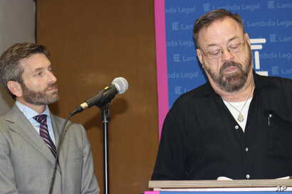 John East, left, and attorney Scott Schoettes discuss a lawsuit that the advocacy group Lambda Legal filed, Feb. 20, 2014, against three Louisiana insurance companies. Schoettes resigned in protest in June from the Presidential Advisory Council on HI...
