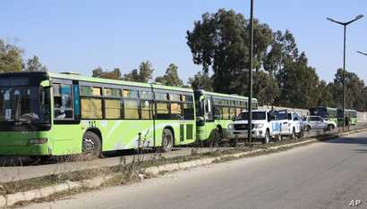 Buses carrying gunmen leave the Waer neighborhood, in the central city of Homs, Syria, as part of a local deal with government forces that allows them safe passage to areas in the country's north, Dec. 9, 2015.