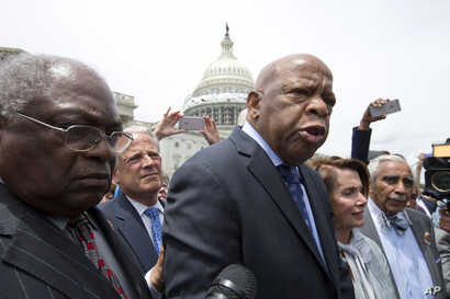 Rep. John Lewis, D-Ga., third from left, accompanied by fellow lawmakers, speaks on Capitol Hill in Washington after House Democrats ended their sit-in protest, June 23, 2016.
