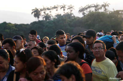Venezuelans liIne up as they cross the Colombian-Venezuelan border over the Simon Bolivar International Bridge outskirts of Cucuta, Colombia Feb. 13, 2019.