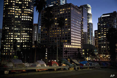 "Homeless tents are dwarfed by skyscrapers as 63-year-old Vincent, who gave only his first name, sorts his belongings, Dec. 1, 2017, in Los Angeles. Vincent said he never had to worry about getting a job as a young man. ""Things ain't the way they wer..."