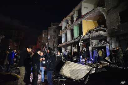 People gather in the aftermath of a multiple explosive attack in the Sayyida Zeinab area, 10 kilometers south of Damascus, Syria, Feb. 21, 2016. The Islamic State group claimed responsibility for a triple blast in the Shi'ite suburb.